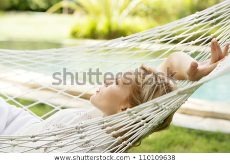 Beautiful blonde young girl relaxed on hammock profile  stock photo © lunamarina