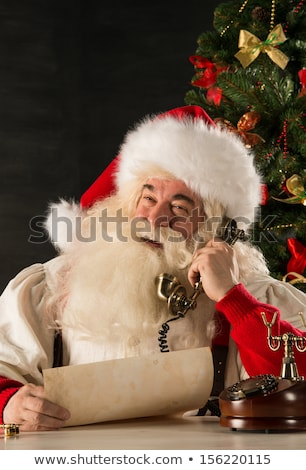 santa claus calling with vintage phone while reading an old roll stock photo © hasloo