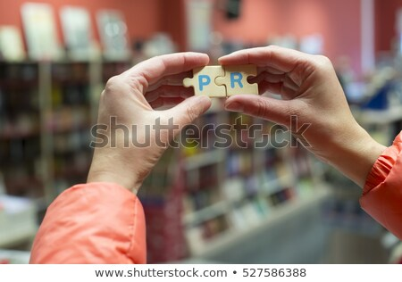 Public Relations word on puzzle in man hands Stock photo © fuzzbones0