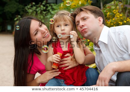 Little girl in red dress with father and mother, starts up soap bubbles in park, in warm afternoon. Stock photo © Paha_L