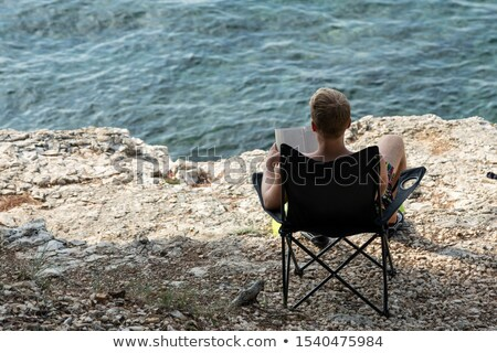 young man sunbathes on beach with stones on back Stock photo © Paha_L