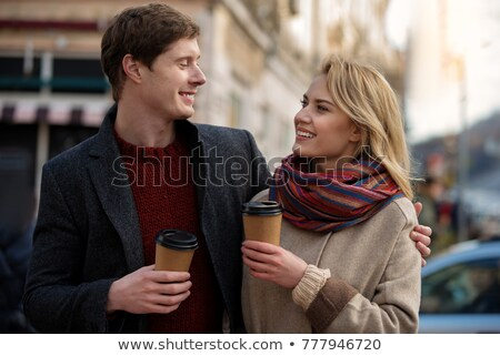 Charming cute lady hugging cup of warm tea and smiling  Stock photo © deandrobot