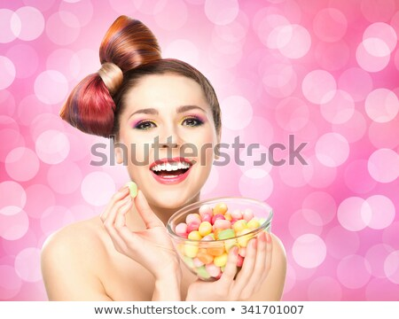 Beautiful cheerful young woman eating jelly candies  Stock photo © deandrobot