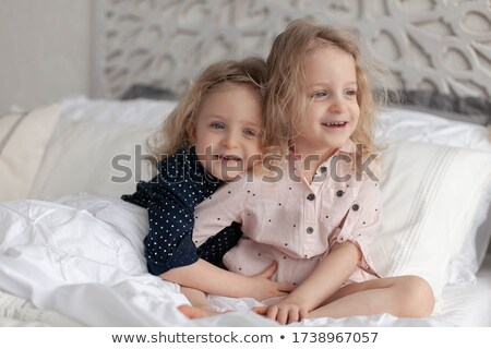 two happy sisters twins sitting on bed and laughing stock photo © deandrobot