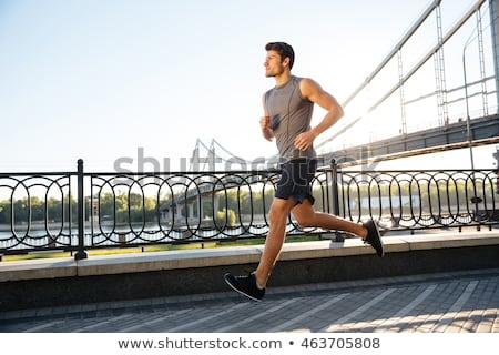 Handsome fit man running fast along big modern bridge Stock photo © deandrobot