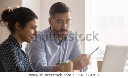 Young businessman working at computer laptop with the finance report on the screen. Business Researc Stock photo © Customdesigner