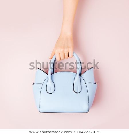 Cute woman holding handbag Stock photo © konradbak