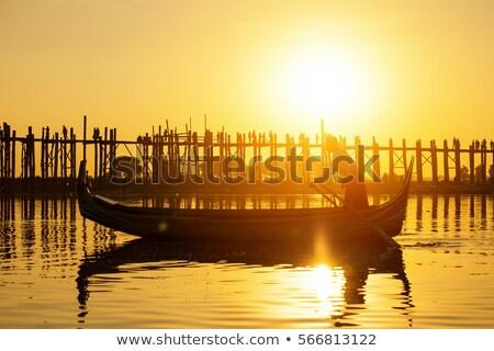 Fishman Under U Bein Bridge At Sunset Foto d'archivio © cozyta