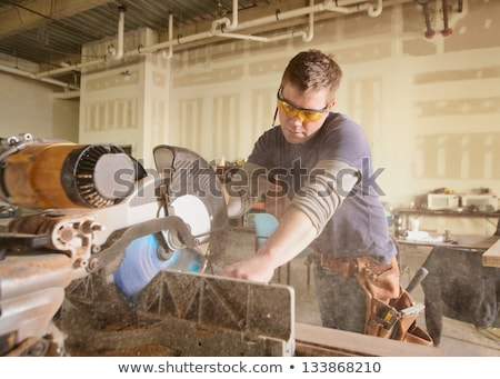 Stock photo: Carpenter handyman using electric handy saw
