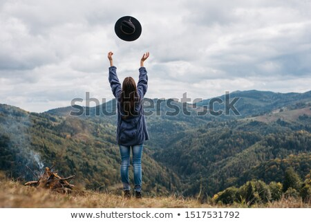 woman on top of hill throwing hat stock photo © is2