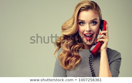 beautiful red-haired lady, speaks to a retro phone Stock photo © balasoiu