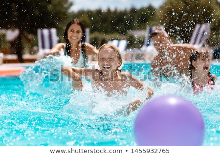 brother and sister in a swimming pool on a summer day stock photo © lightpoet