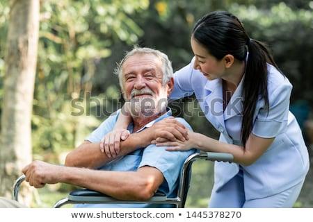 senior man sitting on wheelchair with female nurse stock photo © andreypopov