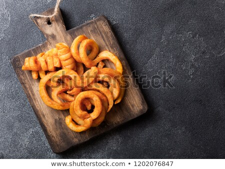 Curly fries fast food snack in paper container on stone kitchen background. Unhealthy junk food Stock photo © DenisMArt