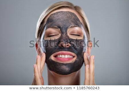 Mosolyog fiatal nő faszén arc maszk szürke Stock fotó © AndreyPopov
