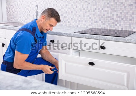 Male Carpenter Installing Door Of Drawer In The Kitchen Stock photo © AndreyPopov