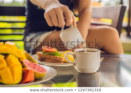 the moment pouring milk into coffee woman pouring cream in coffee stock photo © galitskaya