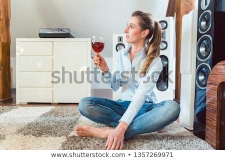 Woman having glass of wine in front of Hi-Fi speakers Stock photo © Kzenon
