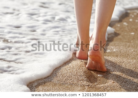 Woman's Feet Walking On Sandy Beach Stock photo © AndreyPopov