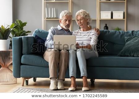 Starszy posiedzenia sofa bawialnia mąż sieci Zdjęcia stock © pressmaster