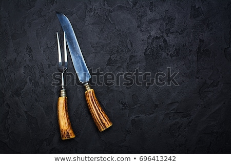 Vintage meat knife and fork on black table background. Butcher utensils. Space for text Stock photo © DenisMArt