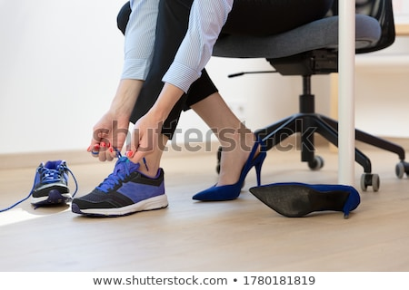 Businesswoman Changing Shoes In Office Stock photo © AndreyPopov