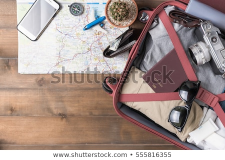packed suitcase with travel accessories and money on wooden background stock photo © galitskaya
