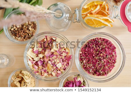 Overview of bowls with dry rose petals, pear and orange slices on wooden table Stock photo © pressmaster