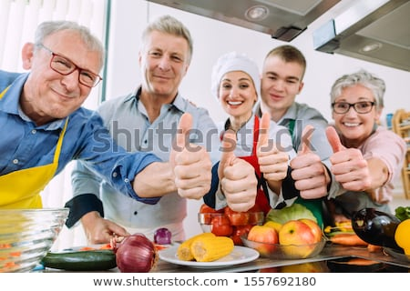 Trainees and their nutritionist in a training kitchen showing thumbs Stock photo © Kzenon