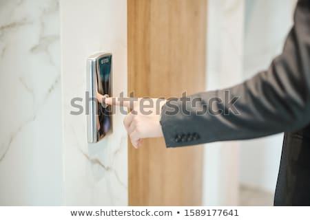 Hand of businessman pushing button on the wall while standing by elevator door Stock photo © pressmaster