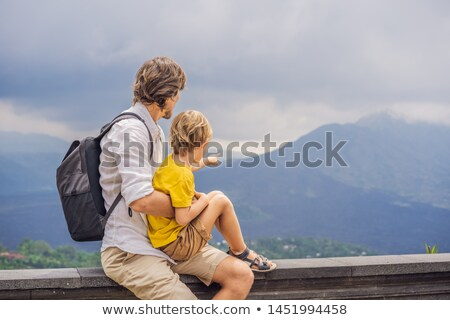 Dad and son tourists on background looking at Batur volcano. Indonesia. Traveling with kids concept Stock photo © galitskaya