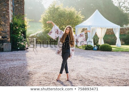 Beautiful woman with long straight hair wears white cape, jeans and high heeled shoes stands crossed Stock photo © vkstudio