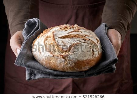 Baker with freshly baked bread in the bakery Stock photo © Kzenon