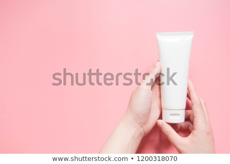female hands holding cosmetic cream tubes. Stock photo © olira
