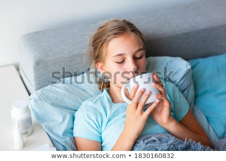 Image of ill caucasian girl holding thermometer and hot tea cup Stock photo © deandrobot