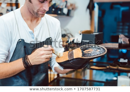 Shoemaker putting glue on sole of a shoe Stock photo © Kzenon