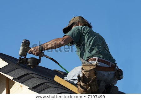 Stock photo: Construction workers put shingles on a roof