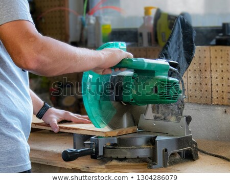 Stock photo: man using miter to saw wood