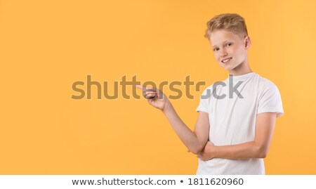 Cheerful young kid pointing towards the camera Stock photo © stockyimages