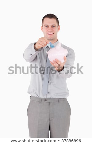 Portrait of a young businessman putting a note in a piggy bank against a white background Stock photo © wavebreak_media