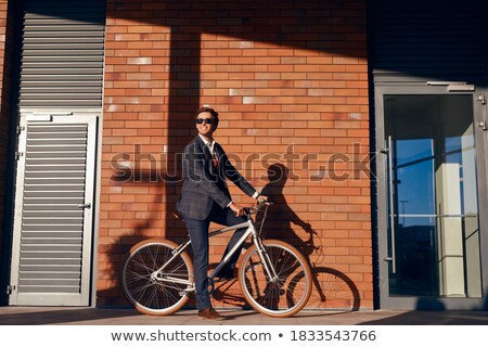 Stock photo:  man looks away while sitting on the sidewalk