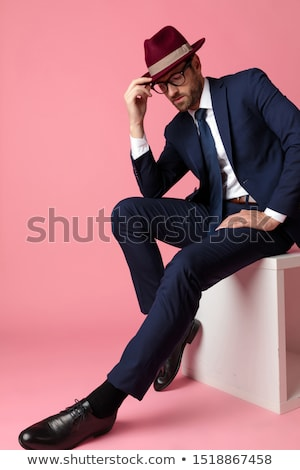 young business man fixing his hair while looking down Stock photo © feedough