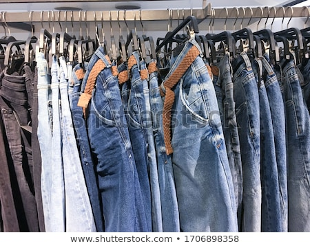 stack of folded blue jeans with jean belt stock photo © illustrart
