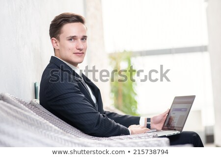 Businessman thinking while showing a mobile phone Stock photo © imagedb