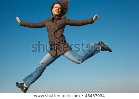 Girl in coat and jeans in jump against blue sky. In bright autumn day. stock photo © Paha_L