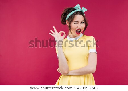 Smiling beautiful pinup girl in headband winking Stock photo © deandrobot