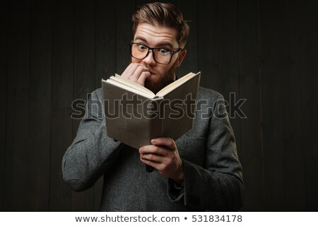 Nervous man in eyeglasses reading book and biting nails Stock photo © deandrobot