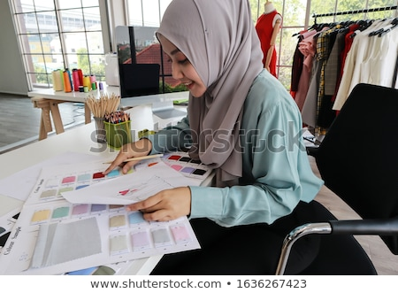 young woman designer choosing textile material for her work stock photo © deandrobot