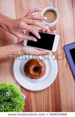 мнение цифровой таблетка чашку кофе пончик деревянный стол Сток-фото © wavebreak_media