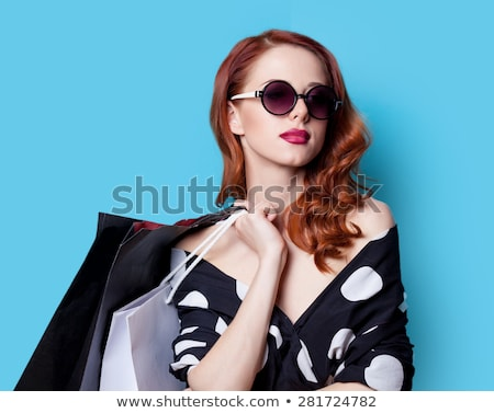 Beautiful redhead girl in sunglasses on blue background. Stock photo © NeonShot